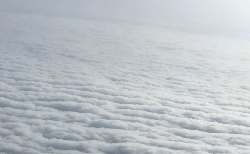 Seen from a plane above the clouds, horizon fills with alternating strips of sun-white and shadow-grey.
