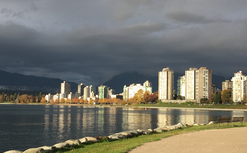View of downtown Vancouver from Vanier Park under storm-grey clouds while light breaks across the skyscrapers that face the sun.
