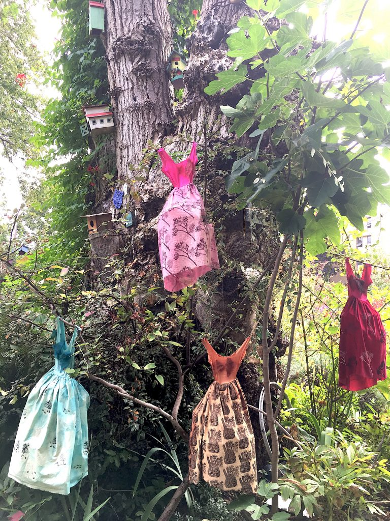 Installation project of four colourful miniature dresses in a tree